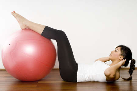 crunch: A young attractive asian woman doing a fitball crunch in a studio Stock Photo