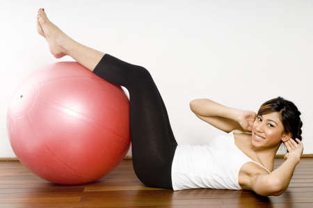 crunch: A young asian woman performing an abdominal crunch on a red fitball Stock Photo