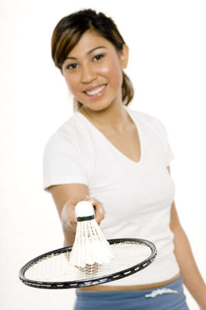 A young woman holding a badminton racket with shuttlecock on top