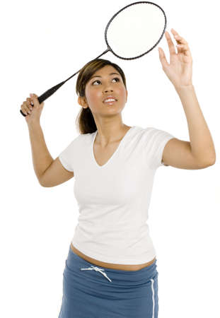 A young woman playing badminton in studio on white background