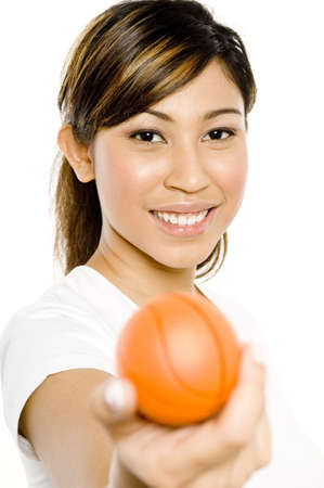 A young attractive asian woman holding a small orange basketball photo