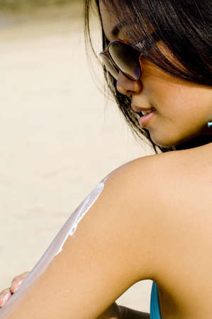 applies: A young woman applies suncream whilst on the beach Stock Photo
