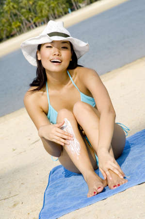 A young attractive asian woman sitting on a beach towel on sandy beach rubbing in sunscreen photo