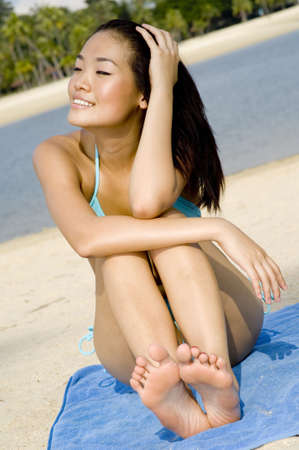 A young attractive asian woman in blue bikini sitting on a tropical beach photo