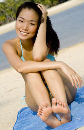 A sexy young asian model sitting on a tropical beach photo
