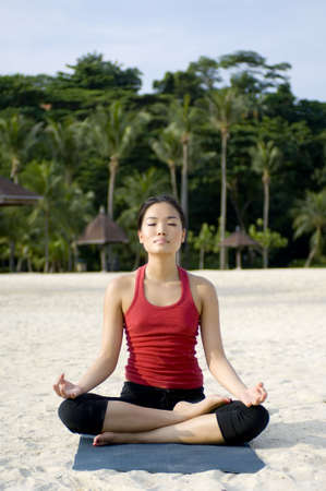 A young asian woman relaxes by doing yoga on the beach photo