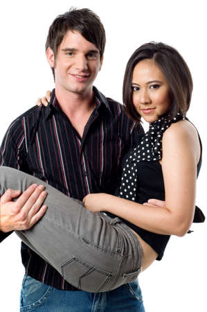 carrying girlfriend: A young man holding his girlfriend in his arms