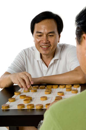 Two Chinese men in their fifties playing chess in the studio photo