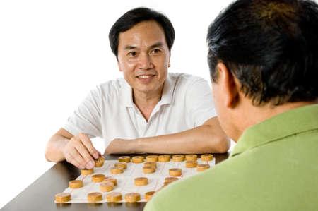 Twee Chinese mannen in hun vijftiger jaren schaken in de studio