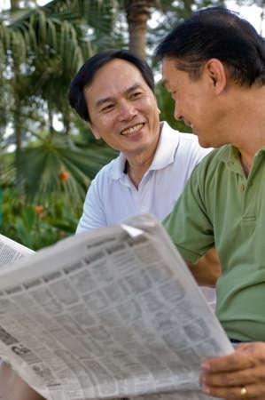 Twee Chinese mannen in hun vijftiger jaren het lezen van de krant in het park