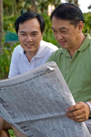 Twee Chinese mannen in hun jaren vijftig lezen van de krant in het park