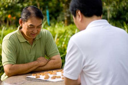 Twee Chinese mannen in hun jaren vijftig spelen schaak in het park
