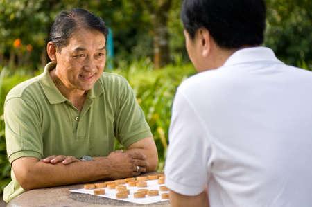 jugando ajedrez: Dos hombres chinos en sus cincuenta jugar ajedrez en el parque