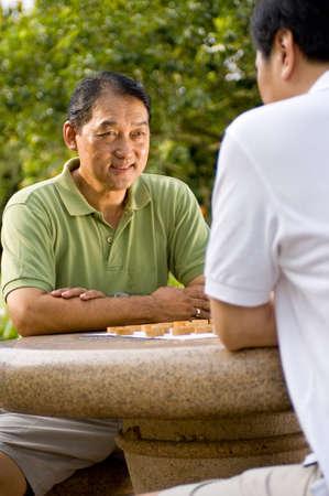 Twee Chinese mannen in hun vijftiger jaren schaken in het park