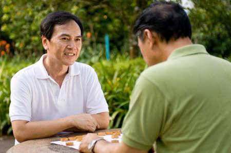 Twee Chinese mannen vijftigers spelen schaak in het park