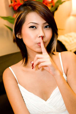 beautification: A young attractive Asian woman with her finger on her lips