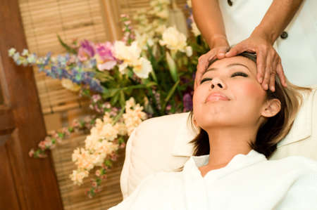 beautification: A young Asian woman having a head massage in a beauty salon