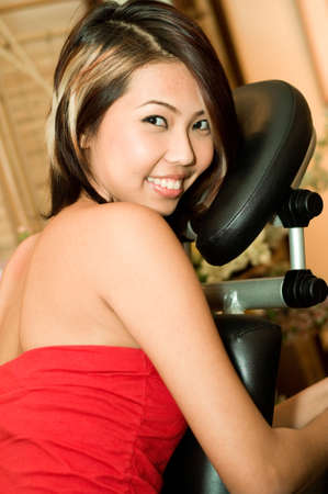 A young Asian woman sitting in a massage chair in a salon