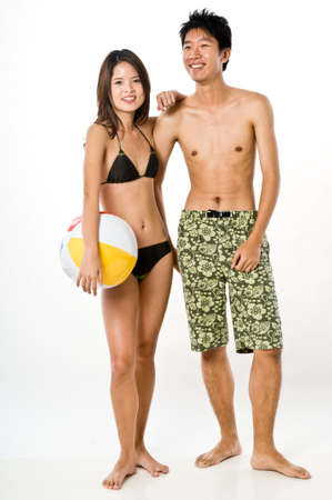 A young attractive couple in beachwear on white background photo
