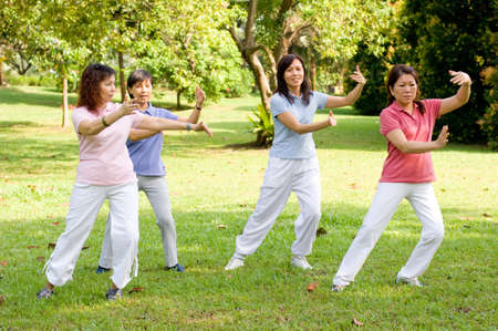 tai chi: A group of asian ladies exercising in the park