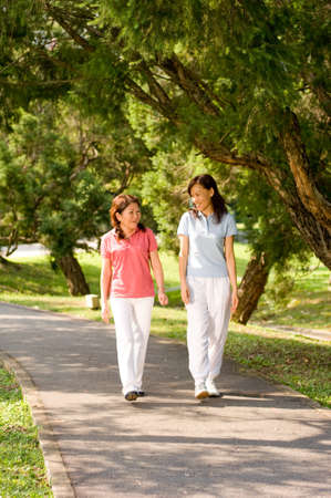 fourties: Two Asian women walking in the park talking to each other