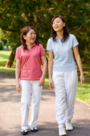 walk in the park: Two Asian women walking in the park talking to each other