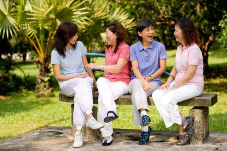 ecoute active: Quatre femmes d'origine asiatique assise sur un banc dans un parc et discuter