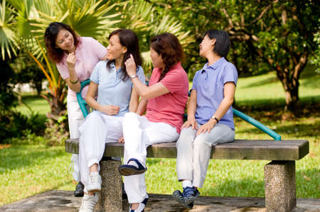 gossiping: Four Asian women sitting on a bench in a park and talking