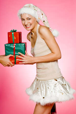 A pretty young woman in sexy santa hat and skirt with gifts on pink background Stock Photo - 1613318