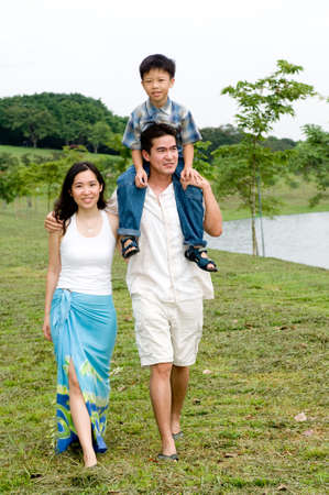 A young couple with their young son walking by a lake Stock Photo