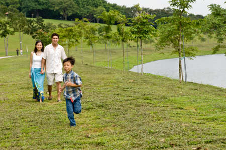 A young couple with their young son running by a lake Stock Photo