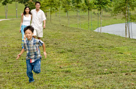 running water: A young couple with their young son running by a lake Stock Photo