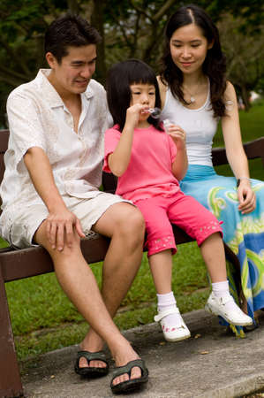 A young couple with a small child spending time together blowing bubbles on a park bench photo