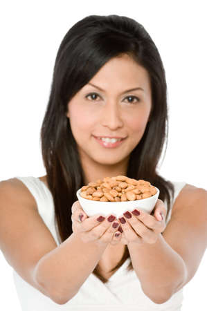 An attractive young Asian woman holding a bowl of almonds on white background Stock Photo - 1693527