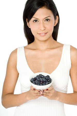 A pretty young Asian woman holding a bowl of blueberries on white background Stock Photo - 1693537