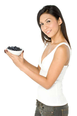 A pretty young Asian woman holding a bowl of blueberries on white background Stock Photo - 1693480