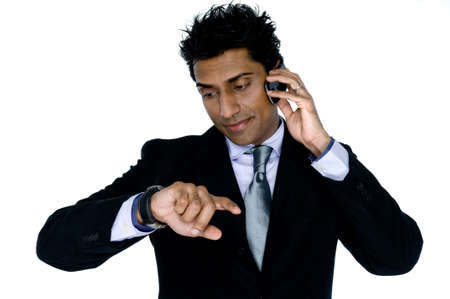 timekeeping: A businessman checks his watch whilst talking on his phone on white background