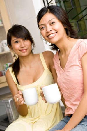 Two women with a mug of coffee or tea photo