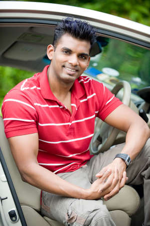 A well-built Asian man in a saloon car in the country photo