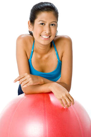 An attractive young Asian woman resting on fitball on white background photo