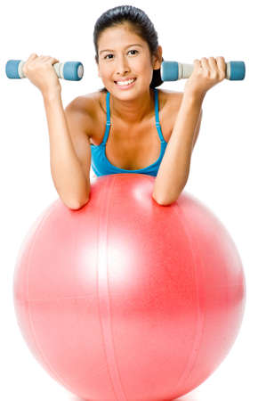 A young woman exercising with fitball and dumbbells on white background photo