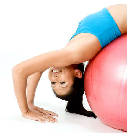 asian abs: A slim young woman stretching over a fitball