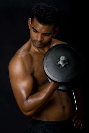 A muscular Indian man with dumbbell on black background photo