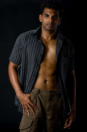 muscle shirt: Un hombre indio muscular en ropa casual sobre fondo negro