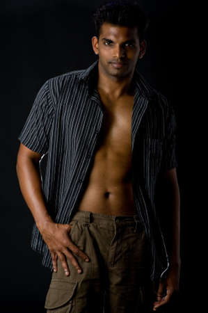 A muscular Indian man in casual clothing on black background photo
