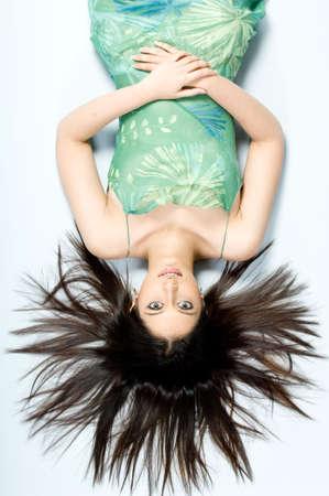 A beautiful woman in green dress lying on studio floor photo