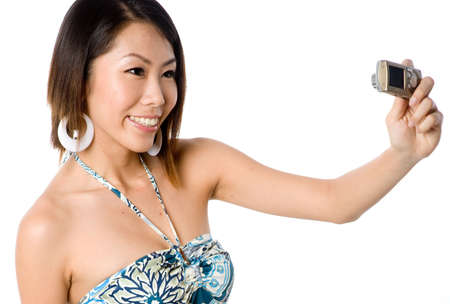 A beautiful Asian woman in summer dress taking her own photo with camera photo