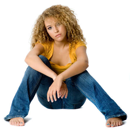 angst: A pretty teenage girl in yellow top and jeans on white background