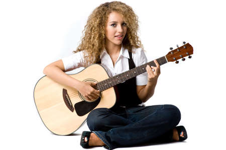 A pretty young woman playing acoustic guitar on white background