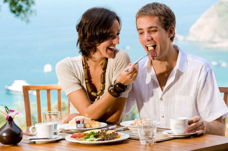 outdoor eating: A young couple enjoying breakfast outside with an ocean backdrop Stock Photo